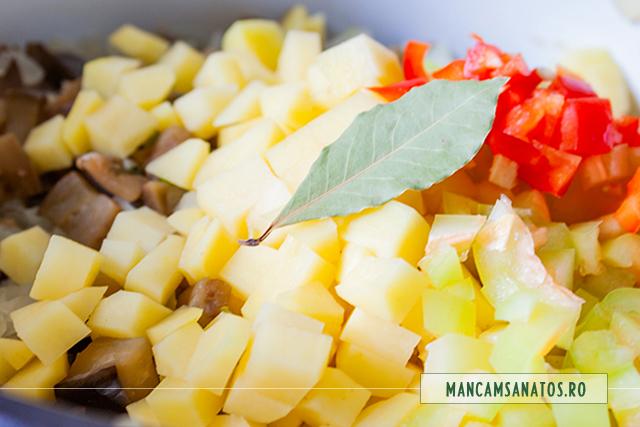 cartofi, ardei si foaie de dafin adaugate la fiert, pentru tocana de vinete si cartofi, cu rozmarin si patrunjel verde