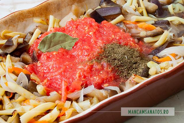 pulpa de rosii si mirodenii adaugate peste alte ingrediente, pentru vinete si fasole verde, picante, la cuptor